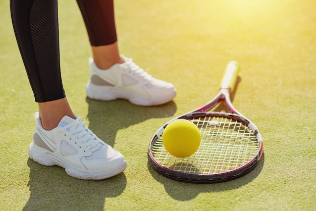 Racket for tennis, ball and female legs in sport sneakers on court close up Premium Photo