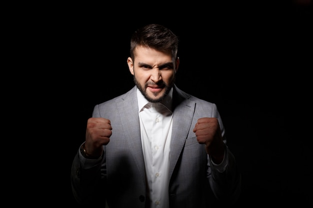 Rage young successful businessman angering over black wall Free Photo