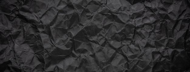 Ragged crumpled dark black paper texture background Premium Photo