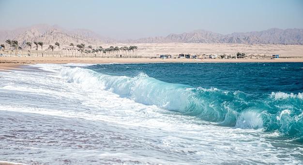 화창한 날씨에 거품 파도와 성난 바다. 산과 해안의 전망. 무료 사진