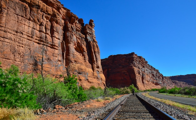 The railroad runs along the red mountains in utah, in the distance is a man between the rails. utah usa Premium Photo