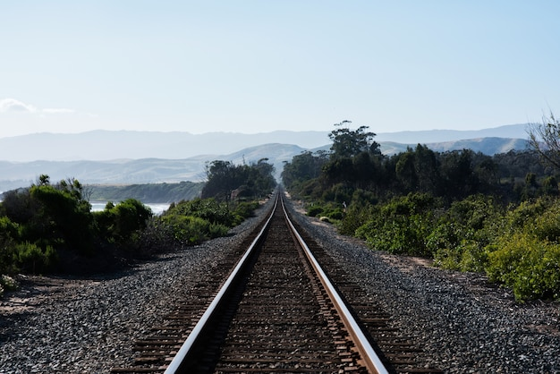 Railroad surrounded by hills and greenery under the sunlight Free Photo