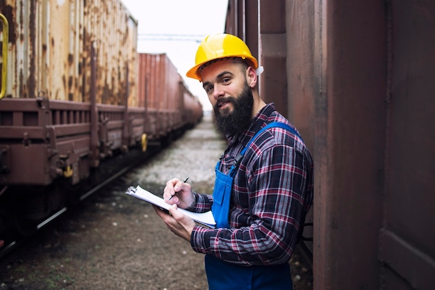 Railroad worker with clipboard standing by the shipping containers and looking to the front Free Photo