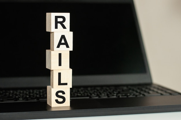 Rails text written on wooden block on computer keyboard . business concept. Premium Photo