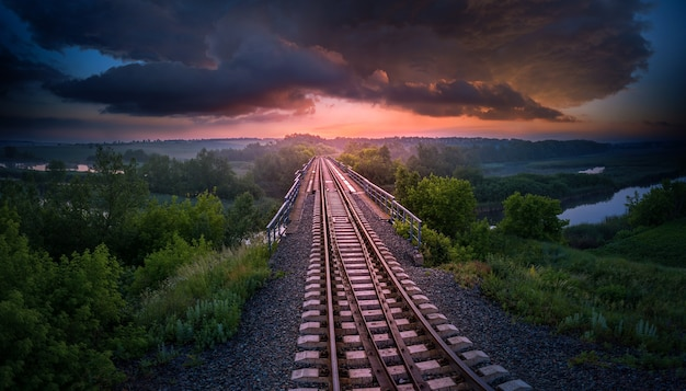 Railway and bridge over the river on a background of sunset and storm clouds. aerial view. beautiful summer evening landscape. Premium Photo