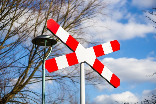 Railway crossing sign against bare trees and cloudy blue sky Free Photo