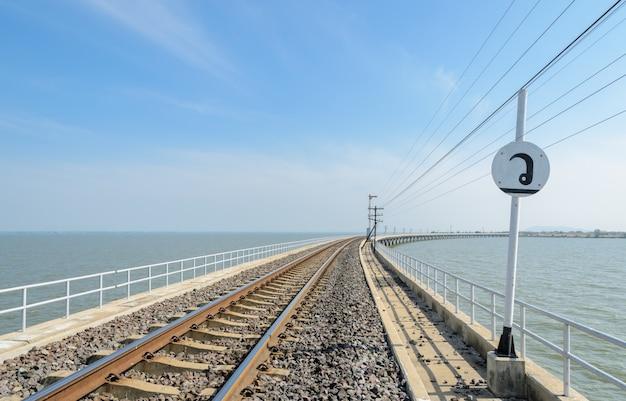 Railway track lead across the lake in thailand Premium Photo