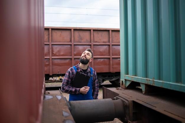 Ferroviario che controlla i rimorchi del treno prima della partenza Foto Gratuite