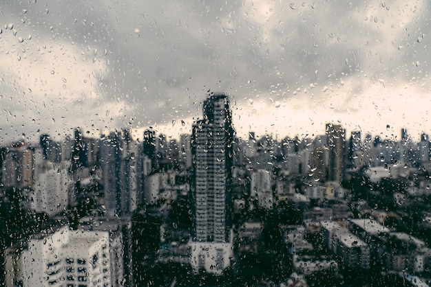 Rain over bangkok: out of focus cityscape behind the window glass with rain drops. Premium Photo