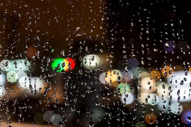 ウィンドウ、夜、クローズアップの背景に雨の滴 Premium写真
