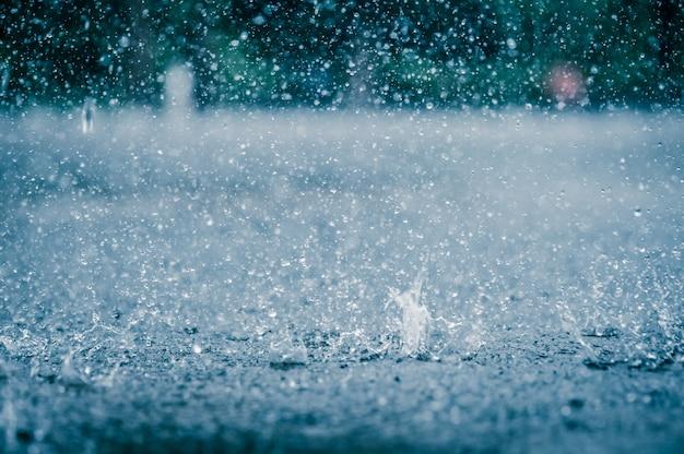 Rain water drop falling to the city street floor in heavy rain day Premium Photo