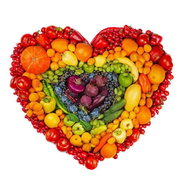 白い背景で隔離の果物と野菜のスタジオの虹の心は菜食主義者の愛の健康的な食事の概念に行きます Premium写真