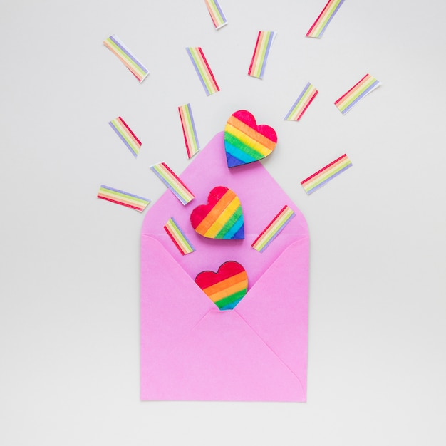 Rainbow heart with paper rainbows scattered from envelope Free Photo