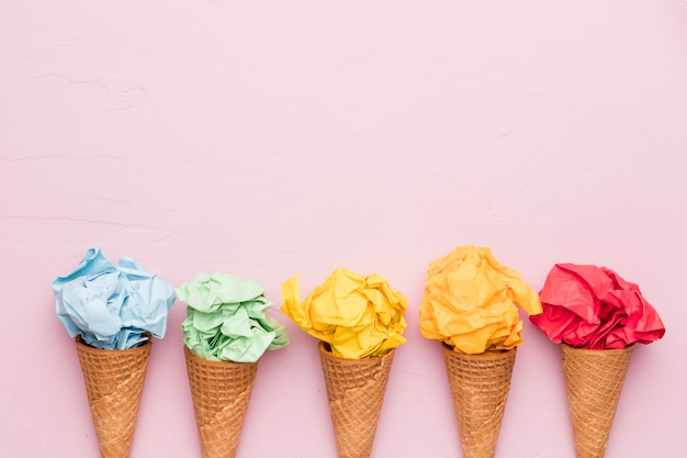 Rainbow ice cream from crumpled colorful paper in waffle cones Premium Photo
