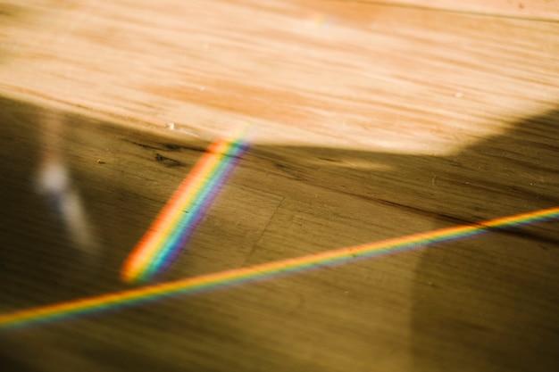 Rainbow light on wood table Free Photo