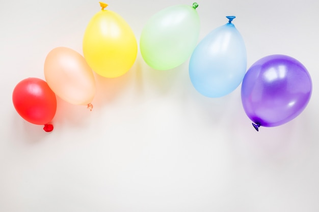 Rainbow made of air balloons on table Free Photo