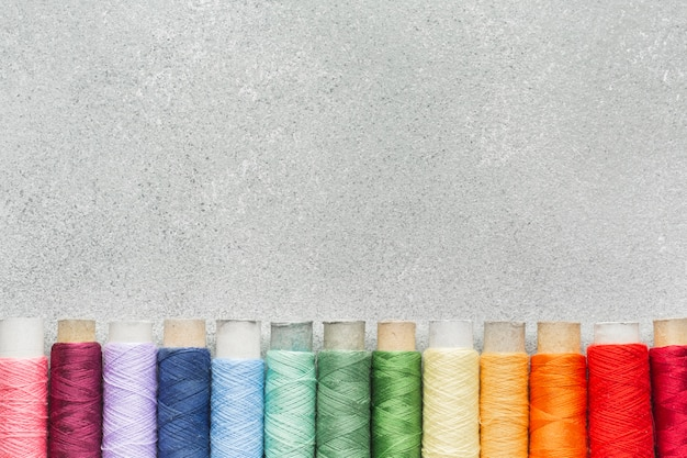 Rainbow multicoloured sewing threads with copy space Free Photo