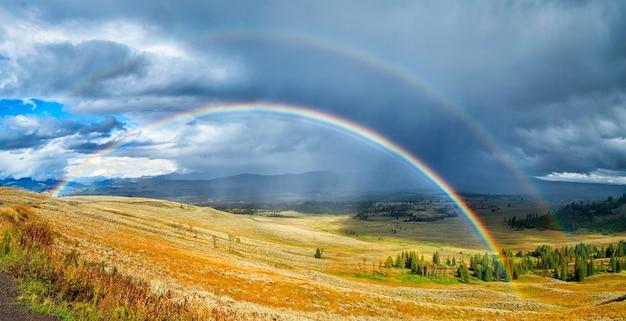 曇り空の下の美しい緑と黄色のフィールド上の虹 無料写真