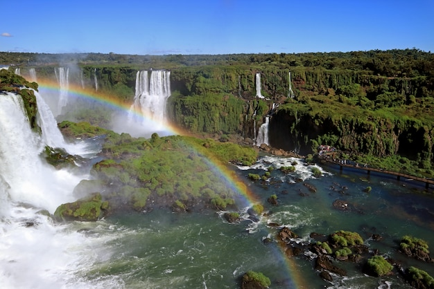 Rainbow over powerful iguazu falls at brazilian side with many visitors on boardwalk, foz do iguacu, brazil Premium Photo