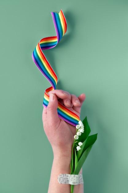 スズランの花を持つ成熟した女性の手にレインボーリボン。医療補助パッチ付きのブーケ。 nhsの医師と看護師に感謝します! Premium写真