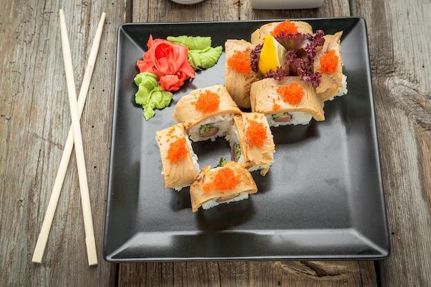 サーモン、ウナギ、マグロ、アボカド、ロイヤルエビ、クリームチーズフィラデルフィア、キャビアトビカ、チュカを添えたレインボー寿司ロール。寿司メニュー。日本食。 Premium写真