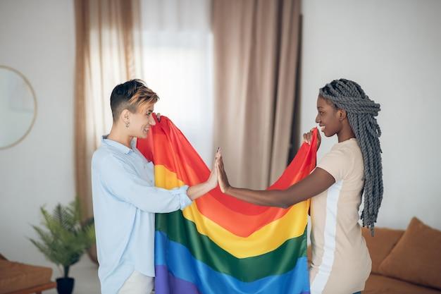 レインボックスフラグ。虹色の旗を持って幸せそうに見える2人の若い女の子 Premium写真