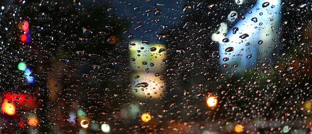 Raindrops on the car windshield during driving on the urban street at night Premium Photo