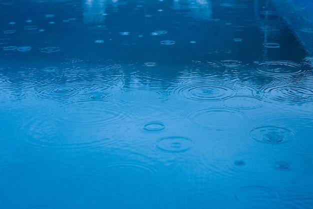 Raindrops falling on a pool or blue lake Premium Photo