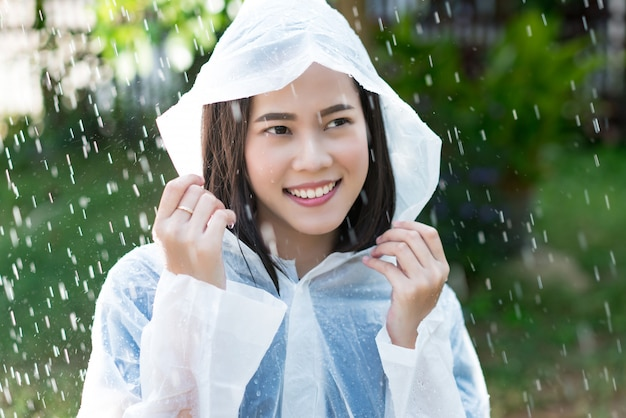 Rainy day asian woman wearing a raincoat outdoors Premium Photo