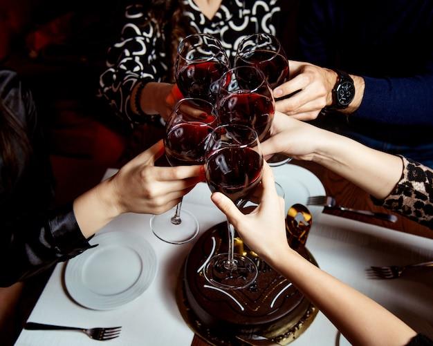 Поднятые бокалы красного вина и шоколадный торт Бесплатные Фотографии