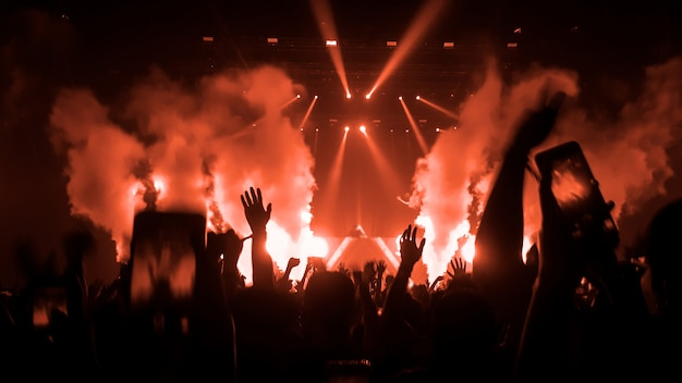 Raised hands silhouettes in a music concert or festival Premium Photo