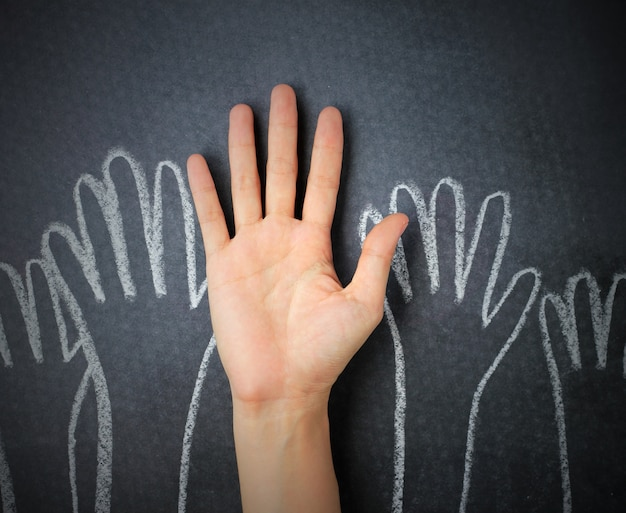 Поднимая руки на фоне доски. рука каракули на фоне доске. Premium Фотографии