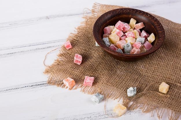 白い木製のテーブルの上のジュート布の上にボウルに多色rakhat-lukum 無料写真
