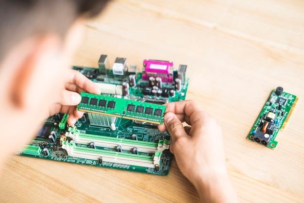 コンピュータマザーボードのramをテーブルでテストしている技術者 無料写真