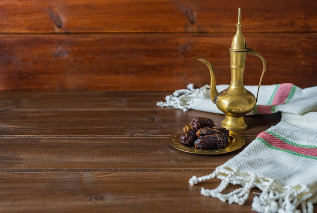 Ramadan food preparation, tea pot with dates, iftar food on wooden background with copy space Premium Photo