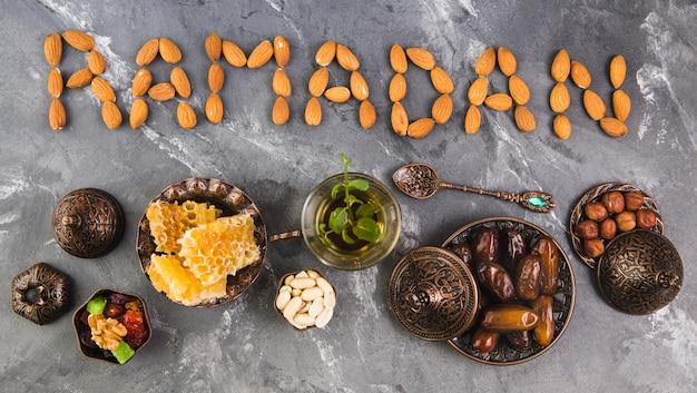Ramadan inscription of almonds with tea and dates fruit Free Photo
