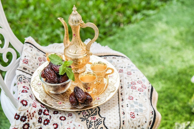 Ramadan inspiration showing date palms in a bowl with golden tea set Premium Photo
