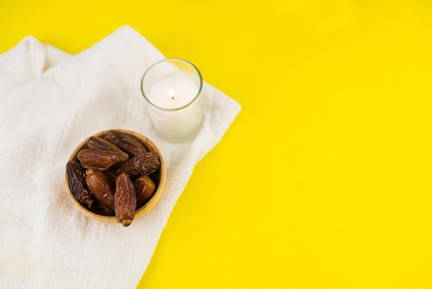ラマダンカリームフェスティバル。黄色の背景にキャンドルをボウルに乾燥した日付フルーツのクローズアップ。コピースペース。 Premium写真