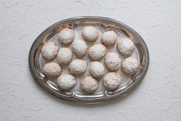 ラマダンのお菓子は、白いテーブルでお茶と一緒にお召し上がりいただけます。エジプトのクッキー「カフエルイード」-エルフィトルイスラムのeast宴のクッキー。上面図。 Premium写真