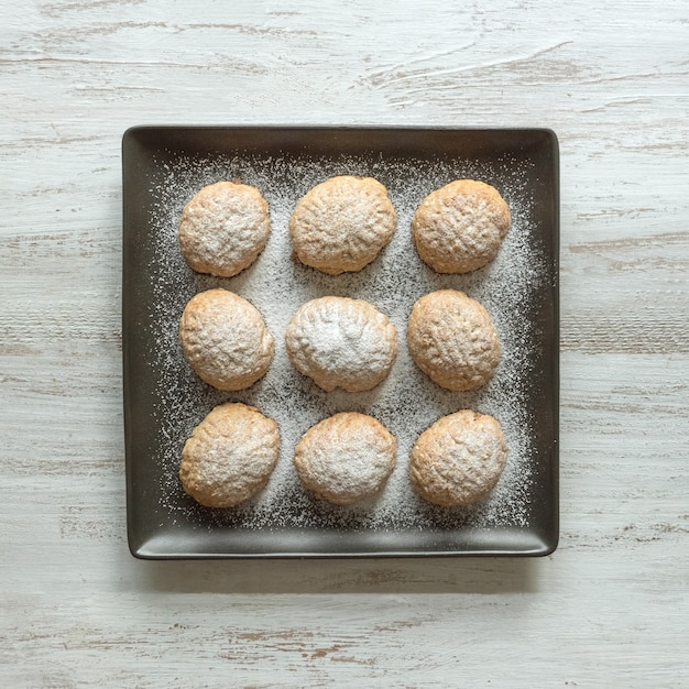 正方形のプレートにラマダンのお菓子。エジプトのクッキー「カフエルイード」-エルフィトルイスラムのeast宴のクッキー。 Premium写真