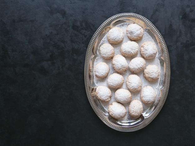 黒いテーブルの上のラマダンのお菓子。エジプトのクッキー「カフエルイード」-エルフィトルイスラムのeast宴のクッキー。トップビュー、コピースペースの背景 Premium写真