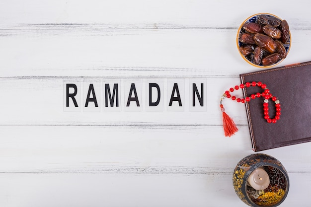 Ramadan text with bowl of juicy dates; diary and red prayer beads on white table Free Photo