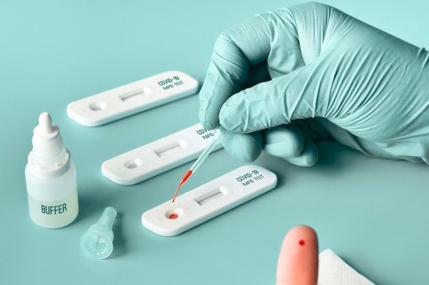 Rapid express covid19 test. medic or doctor applies blood from patient finger on test. Premium Photo