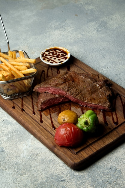 Rare cooked steak served with fries, grilled vegetables and sauce Free Photo