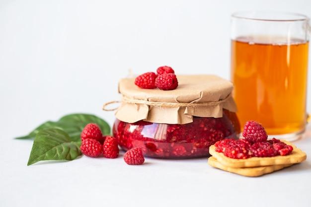 Raspberries with sugar, healthy fresh raspberries, homemade jam in a jar, morning breakfast on light Premium Photo