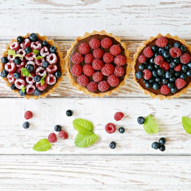 Тарталетки из малины и черники с шоколадным ганашем, свежими ягодами и листьями мяты, выборочный фокус. Premium Фотографии