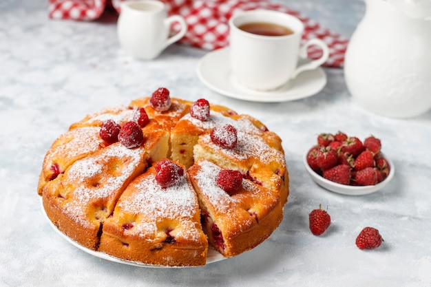 Raspberry cake with powdered sugar and fresh raspberries on a light . summer berry dessert. Free Photo