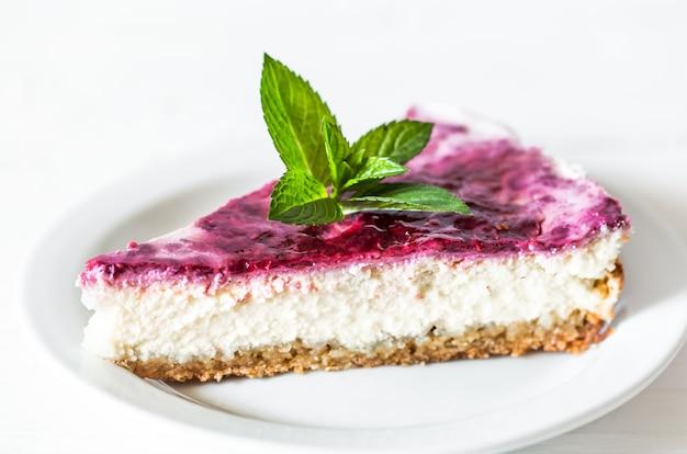 Cheesecake ai lamponi con foglie di menta su sfondo bianco, concetto, pasticceria Foto Gratuite
