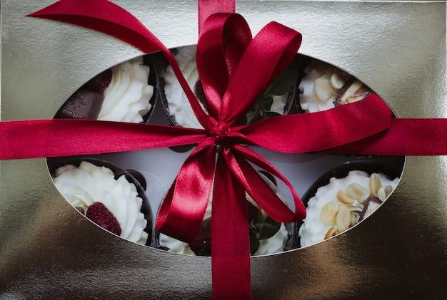 선물 상자에 휘핑 크림과 함께 라즈베리 초콜릿 케이크 프리미엄 사진