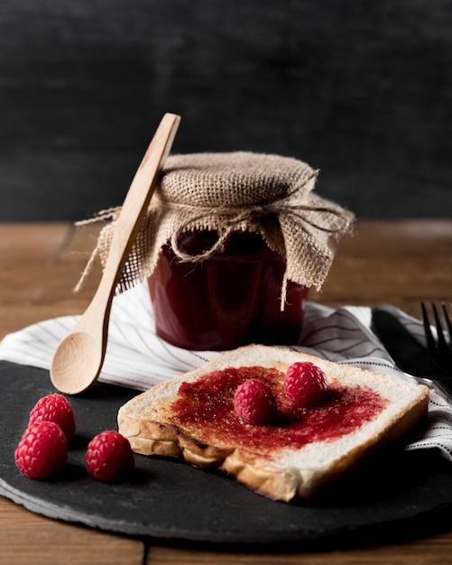 Marmellata di lamponi sul pane con barattolo e cucchiaio Foto Gratuite